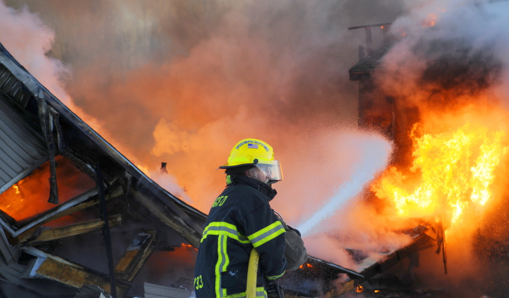 BURNED: Firefighters work at containing a blaze Tuesday at a new home Tuesday in Farmingdale. Several fire companies from surrounding towns responded to the blaze that destroyed the large home off the Hallowell-Litchfield Road.