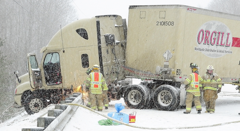 ICY ACCIDENT: Sparks fly as Winthrop firefighters cut the guard rail so that a jackknifed tractor-trailer stuck on it can get towed away on Thursday following a collision between it and a car on U.S. Route 202 in Winthrop.