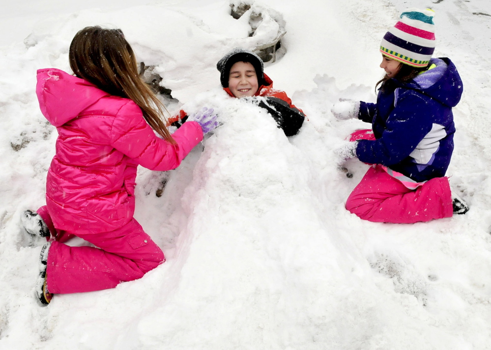 HAPPY DAYS: These kids got an early dismissal day on Thursday, because of the snowstorm and time to play outdoors. Burying Nicholas Bradley up to his neck in snow is Hannah Kellam, left, and Danielle Bradley.