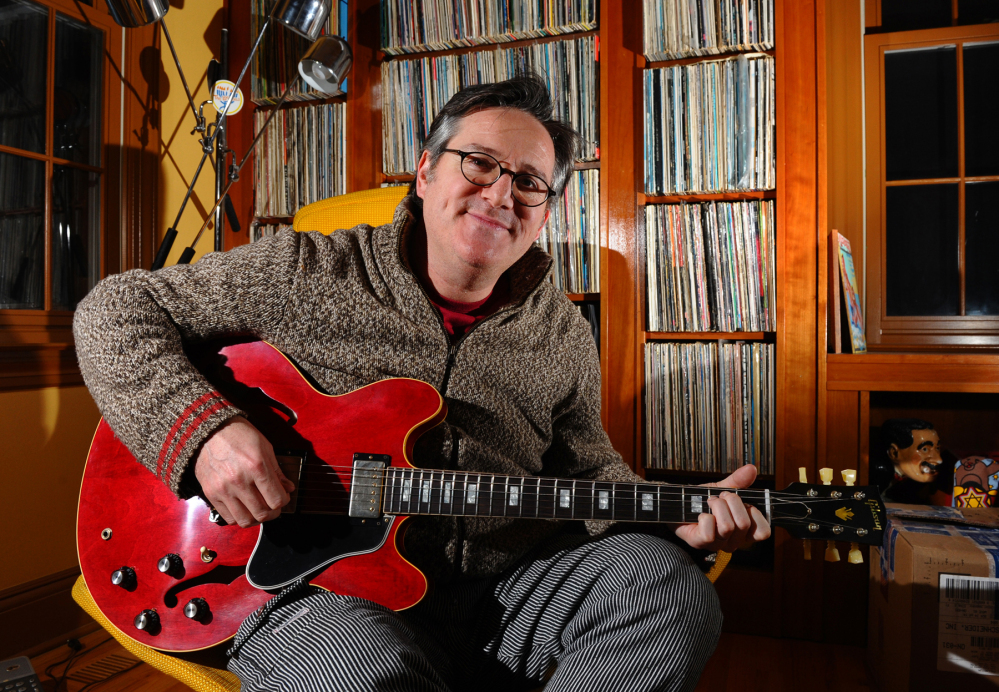 David Schneider poses with his new custom Gibson guitar at his home in Fairfield, Conn. It was given to him by Gibson after hearing of his plight of a Gibson guitar that was broken during baggage handling at Delta Airlines.