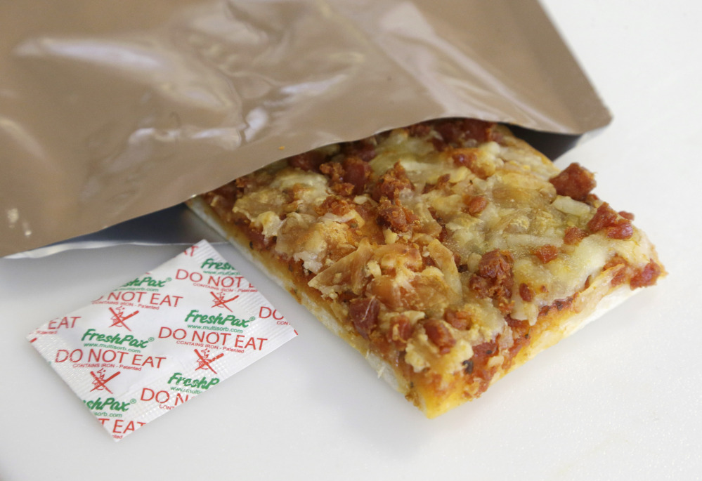 A slice of prototype pizza, in development to be used in MRE's – meals ready to eat – sits in a packet next to a smaller packet known as an oxygen scavenger, left, at the U.S. Army Natick Soldier Research, Development and Engineering Center.