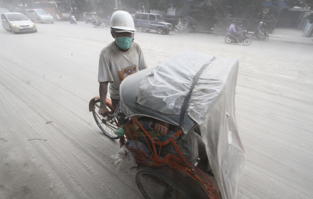 A pedicab makes its way on a street covered with volcanic ash in Solo, Indonesia on Friday