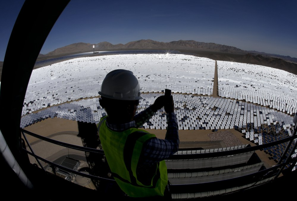 Jeff Holland takes a picture of some of the thousands of computer-controlled mirrors that reflect sunlight to boilers that sit on towers.