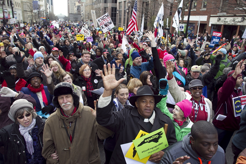 Rev. Jerry Dowdy of Carthage, N.C., sings with thousands of others during a march in Raleigh, N.C. Saturday Feb. 8, 2014. Nearly 200 organizations are joining the National Association for the Advancement of Colored People in the