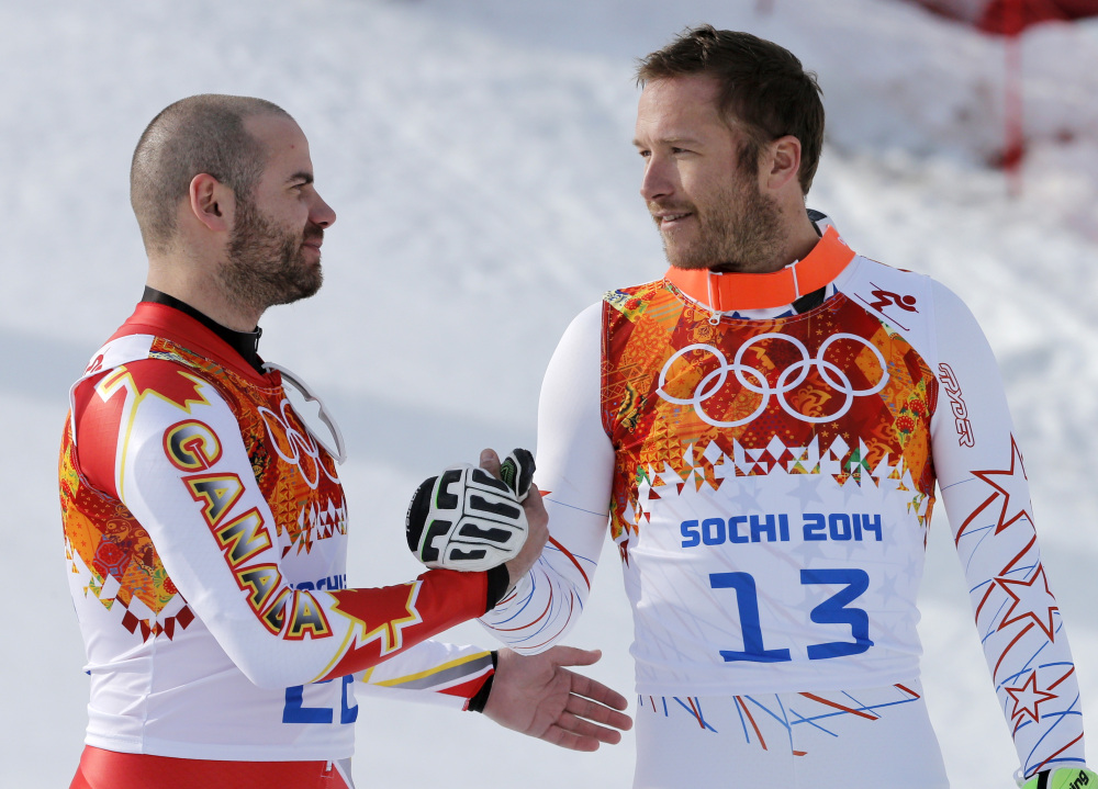 Men's super-G joint bronze medal winners Canada's Jan Hudec and United States' Bode Miller shake hands on the podium during a flower ceremony at the Sochi 2014 Winter Olympics on Sunday in Krasnaya Polyana, Russia.