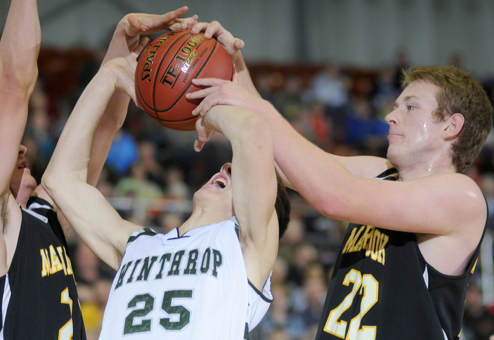 Staff photo by Andy Molloy Maranacook Community School's Cameron Brochu, left, and Brad Worster block Winthrop High School's Dakota Carter during a tournament basketball match up Monday against in Augusta.