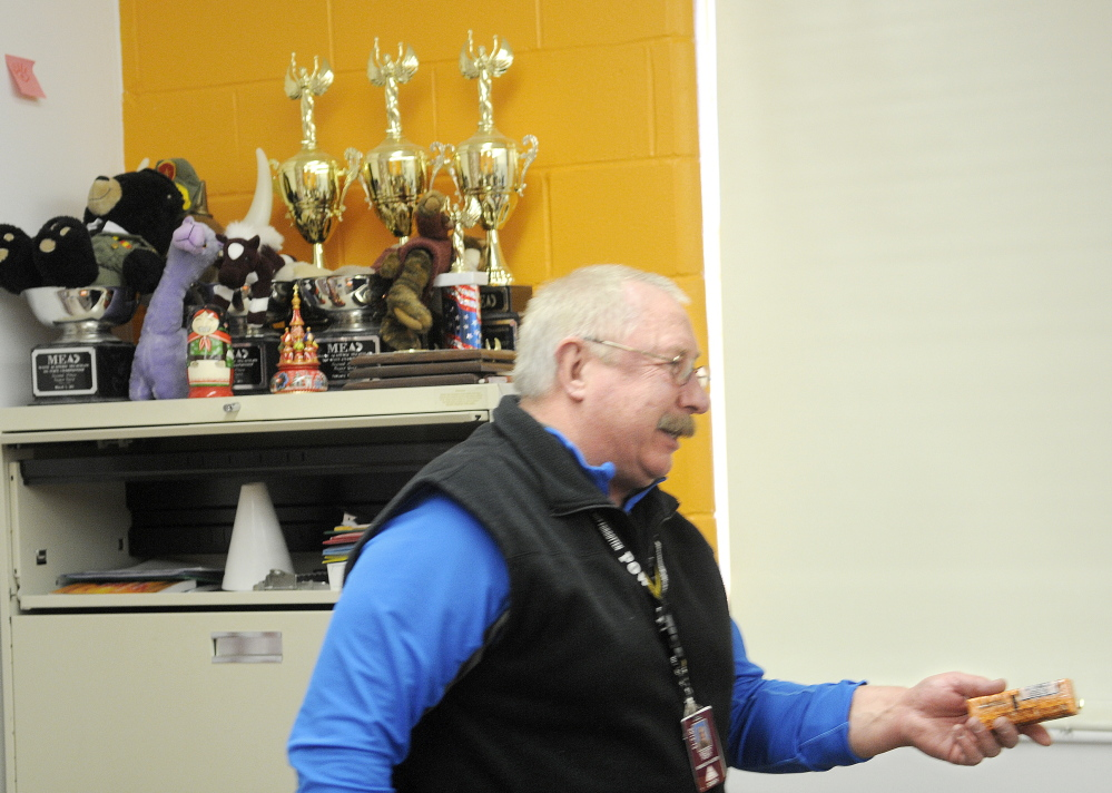 CONDITIONING: Retired teacher and Academic Decathlon coach Scott Foyt hands out crackers to Monmouth Academy's Academic Decathon team during a recent practice. Foyt and his wife, Cathy, have coached the school's team for several years at the Monmouth school.
