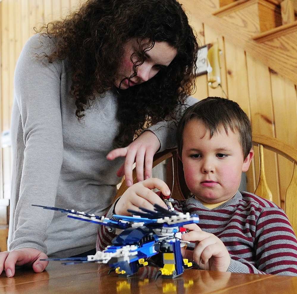 BUILDING: Kimberlee Lewis, left, helps her brother, Nate Lewis, build a Lego set that their father, Maj. Scott Lewis, sent him as a Valentine's Day gift on Friday February 14, 2014, in Monmouth.