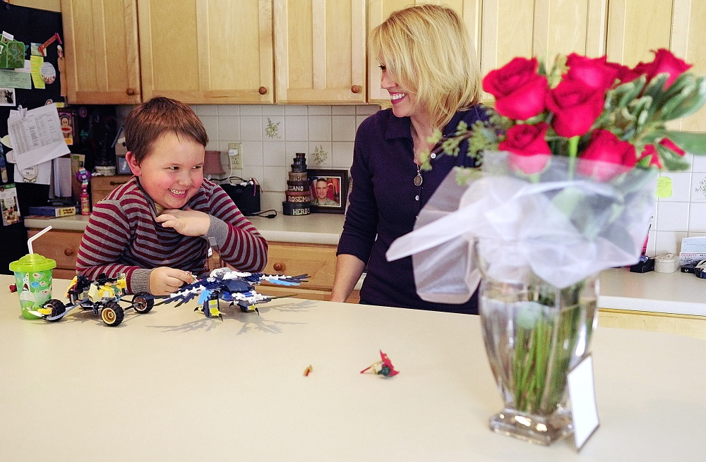 REMEMBERING: Nate Lewis, 6, laughs with his mother Lynn Lewis on Friday February 14, 2014, at their home in Monmouth. Maj. Scott Lewis, who is serving in Afghanistan, sent his son the Lego set and his wife the vase of roses for Valentine's Day.