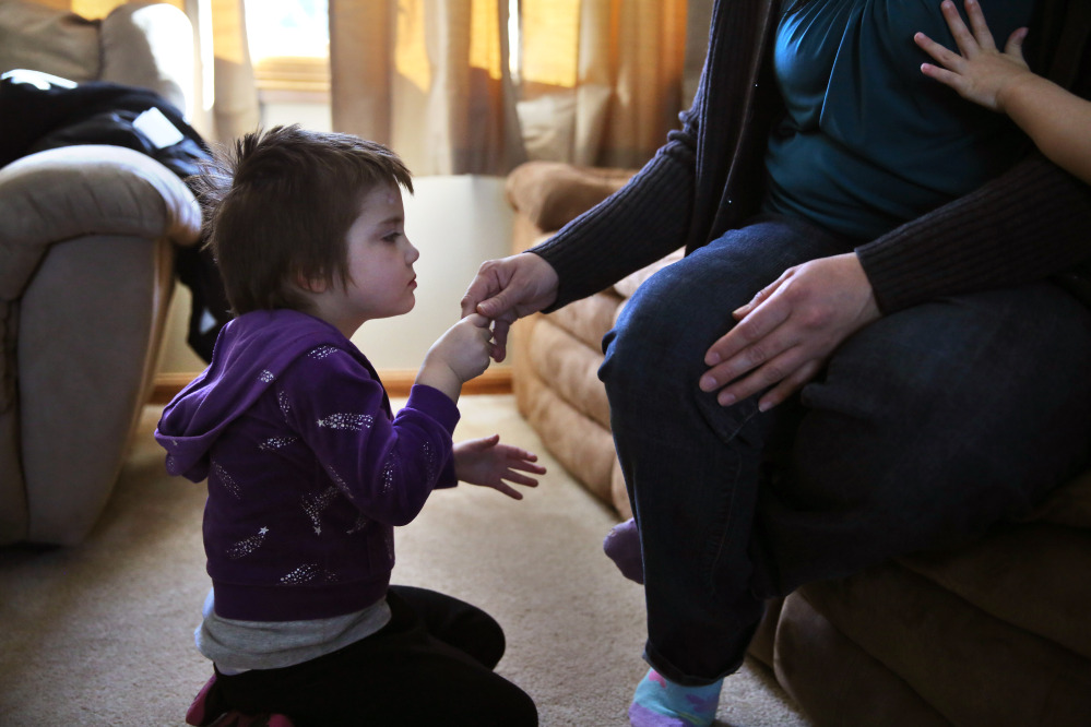 Elizabeth Burger, 4, holds her mother's hand at home in Colorado Springs, Colo. Elizabeth suffers from severe epilepsy and is receiving experimental treatment with a special strain of medical marijuana, which she takes orally as drops of oil.