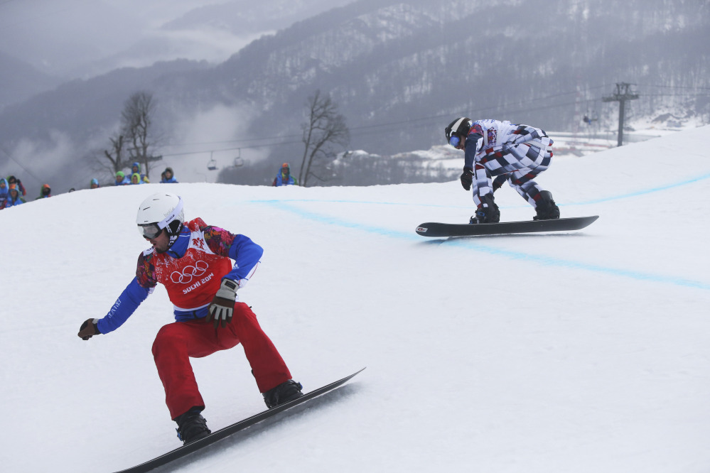 Gold medalist Pierre Vaultier of France, left, leads silver medalist Nikolai Olyunin of Russia, in the men's snowboard cross final at the Rosa Khutor Extreme Park, at the 2014 Winter Olympics, Tuesday, Feb. 18, 2014, in Krasnaya Polyana, Russia.