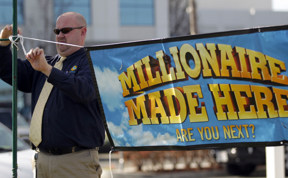 """California Lottery official John Reading hangs a """"Millionaire Made Here"""" sign at the Dixon Landing Chevron that sold a winning $425 million Powerball ticket in Milpitas, Calif. The owners of the station received a $1 million bonus for selling the ticket."""