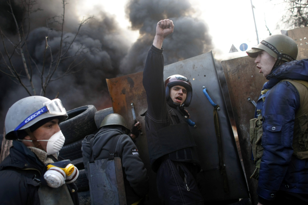 """Anti-government protesters shout """"Glory to the Ukraine"""" as they man a barricade at Independence Square in Kiev on Friday."""