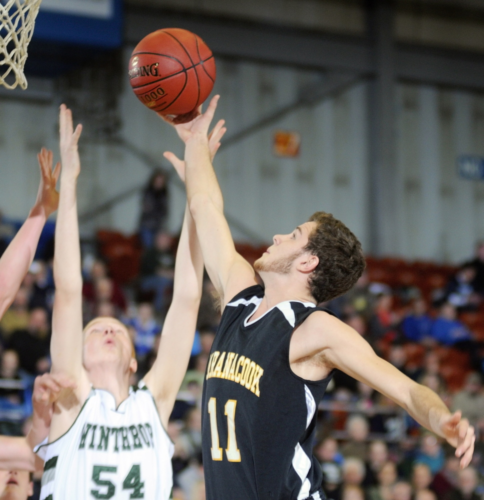 GETTING AFTER IT: Maranacook Community School senior guard Taylor Wilbur, right grabs a rebound in front of Winthrop High School sophomore center Anthony Owens during a Western Class C quarterfinal game Monday in Augusta Civic Center. The Black Bears play Waynflete Saturday for the Western Class C championship.