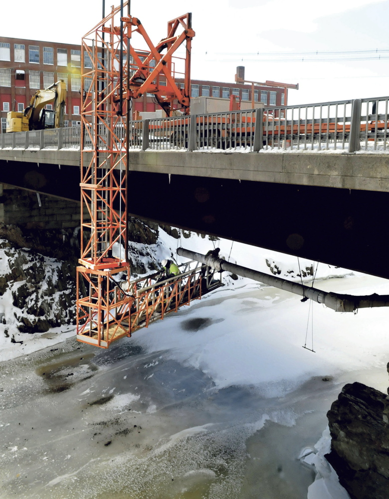 OVER AND UNDER: Workers are suspended under one of the Margaret Chase Smith Bridges in Skowhegan while removing a sewer line recently. Other workers nearby are replacing a pumping station. All the work should be completed by April.