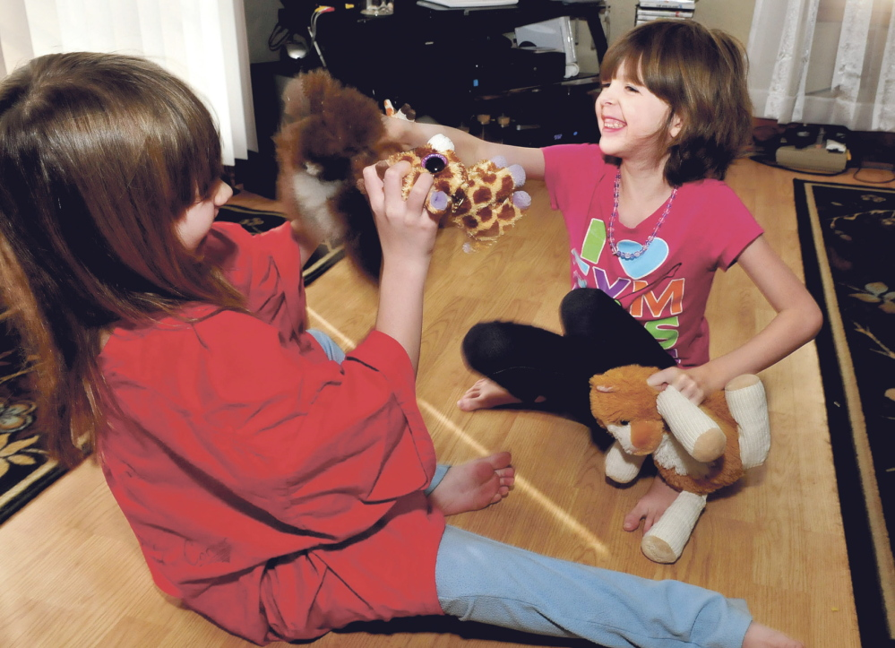 Normal life: Kaitlyn Parker, right, and her sister Briana play with toys Wednesday at their home in Augusta. Kaitlyn is dealing with a medical condition known as Marfan syndrome, a genetic disorder that can affect ligaments and the heart.