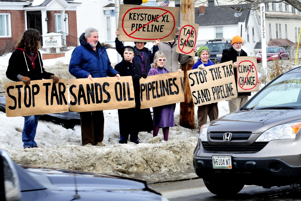 AGAINST: For the second time in February, this group of concerned citizens hold vigil against the proposed Keystone XL Pipeline on Sunday, Feb. 23, 2014, in front of the Universalist Unitarian Church in Waterville. From left in front are Anselm Scheck, Iver Lofving, Jane Edwards, Linda Woods, Marian Flaherty and Dick Thomas. In back are Cynthia and Paul Stoncioff.