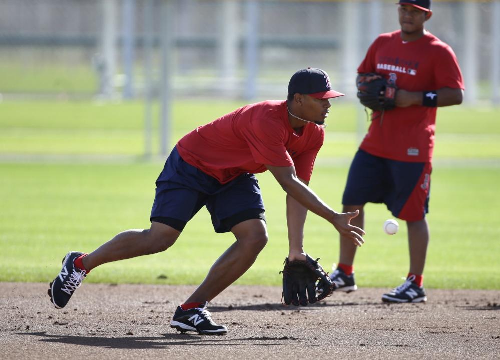 Boston Red Sox infielder Xander Bogaerts fields the ball as infielder Heiker Meneses, right, looks on during spring training baseball practice on Feb. 15, 2014, in Fort Myers, Fla.