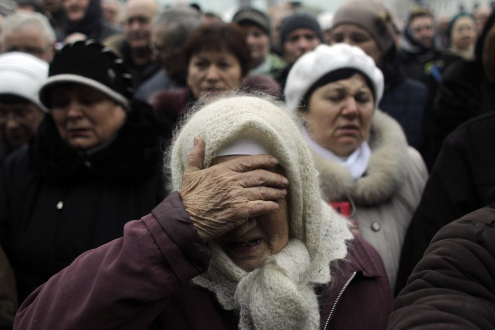 A woman reacts at a memorial for the people killed in clashes with the police at Kiev's Independence Square, the epicenter of the country's current unrest, Ukraine, Tuesday, Feb. 25, 2014.