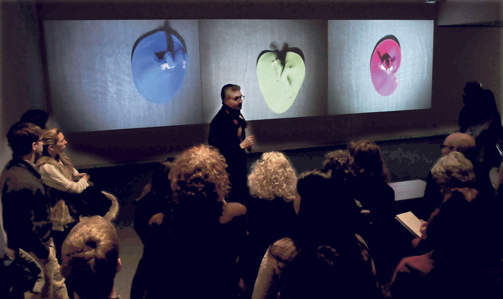 """DAZZLING: Ahmed Abdalla, artist and co-curator of the exhibit """"Histories of Now: Six Artists of Cairo,"""" speaks in front of the video art installation titled """"Merge and Emerge"""" of Egyptian dancers twirling in colorful garments at the Colby College Museum of Art in Waterville on Thursday."""