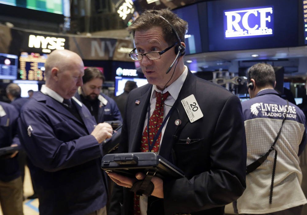 Trader Christopher Forbes, center, works on the floor of the New York Stock Exchange on Wednesday. The Standard & Poor index closed at a record high Thursday.