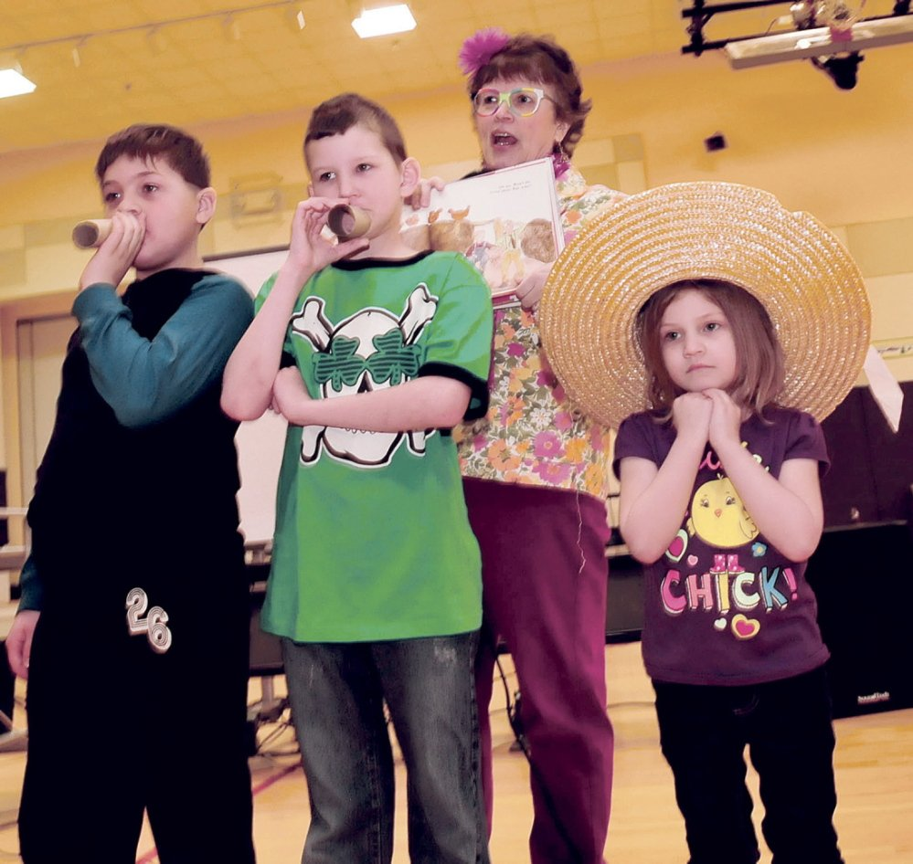 """IN CHARACTER: Author Lynn Plourde directs Madison Elementary School students who were dressed as characters from her new book titled """"You're Wearing THAT To School?"""" on Thursday at the school. From left are Griffin Aldrich, Matt Hurst, Plourde and Alyssa Burrows."""