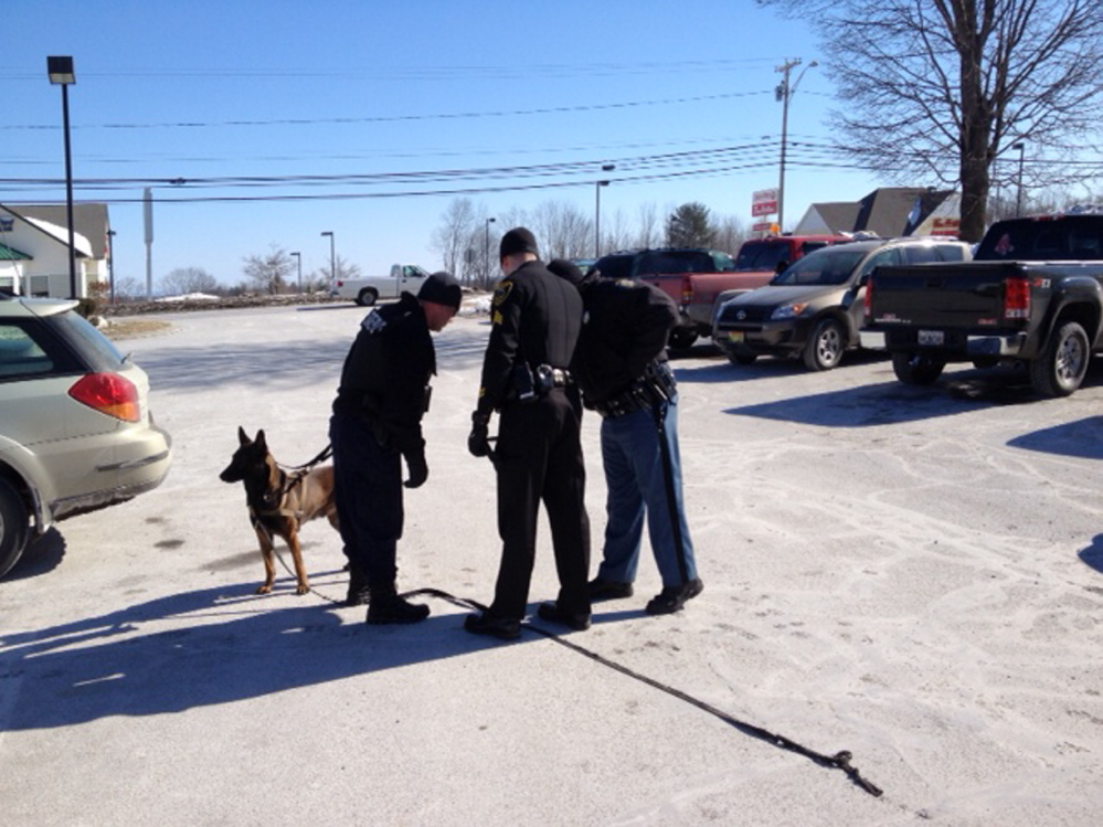 search: Officers with a police dog, Foster, in the McDonald's parking lot off upper Main Street Friday morning during the search for the robber of the nearby Bangor Savings Bank.