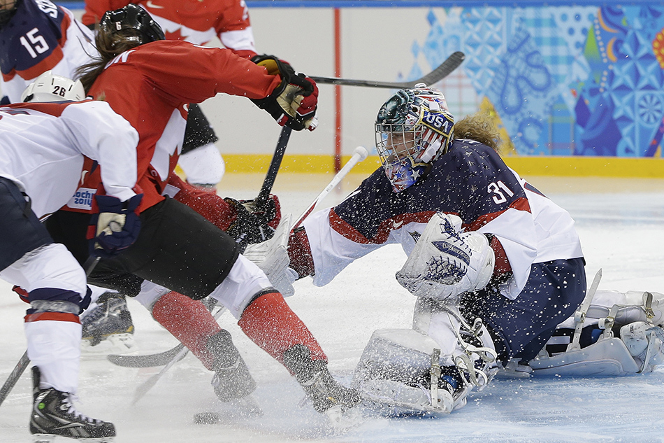 Rebecca Johnston of Canada takes a shot at the goal as USA Goalkeeper Jessie Vetter reaches for the puck during the second period of the 2014 Winter Olympics women's ice hockey game at Shayba Arena, Wednesday, Feb. 12, 2014, in Sochi, Russia.
