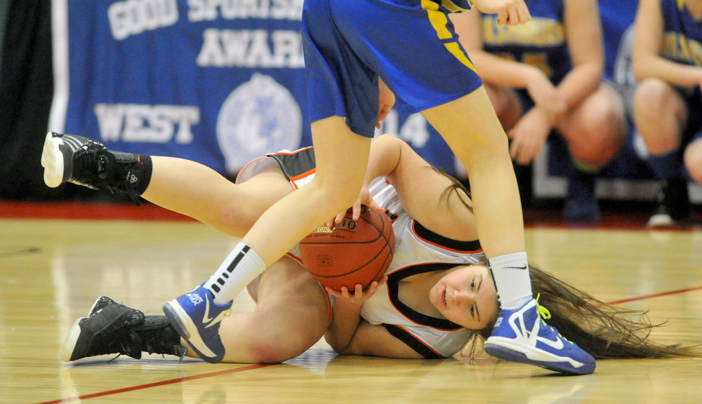 GROUNDED: Forest Hills' Patricia Lessard (40) dives for the loose ball in front of Washburn's Hannah Heald (22) in the Class D state championship game Saturday at the Augusta Civic Center. Washburn defeated Forest Hills 78-40.