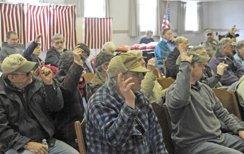 TOWN MEETING: Residents of Cornville vote on a motion during the annual Town Meeting at the Cornville Town Hall on Saturday.