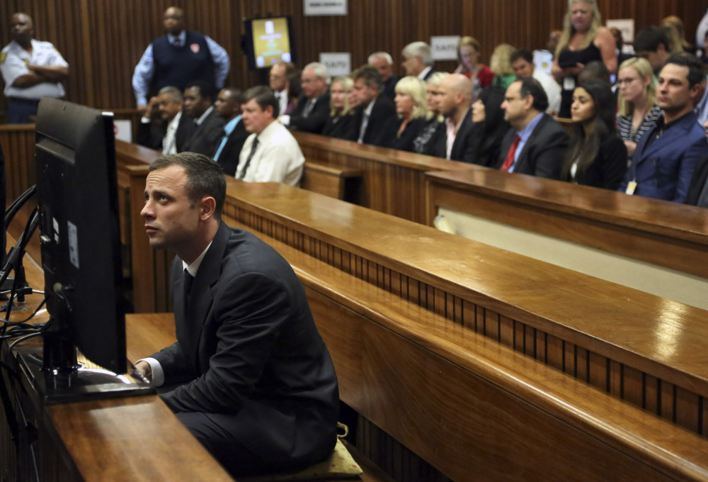 Oscar Pistorius sits in the dock prior to the start of his trial at the high court in Pretoria, South Africa, Monday. Pistorius denies murder and says he killed his girlfriend by mistake when he fired four times through a bathroom door thinking there was a dangerous nighttime intruder on the other side.