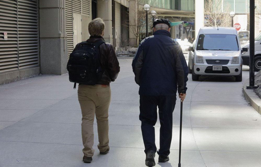 """First-year Northwestern University medical student Jared Worthington walks with his """"Alzheimer's buddy,"""" retired physician Dan Winship in Chicago's Streeterville neighborhood."""