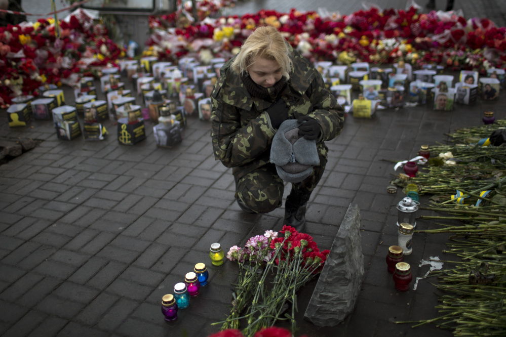 """An Ukrainian woman wearing camouflage uniform pays respect at the site were her friend Ustim Golodniuk was killed in clashes with the police at the Shrine of the Fallen in Kiev's Independence Square, Ukraine, Wednesday, March 5, 2014. The Shrine of the Fallen, located on Institutska Street, honors the fallen """"Heroes"""" of the """"Heavenly Sotnya"""" (Hundred). Over the course of the Euro Maidan protests, almost 100 protesters were killed by police."""