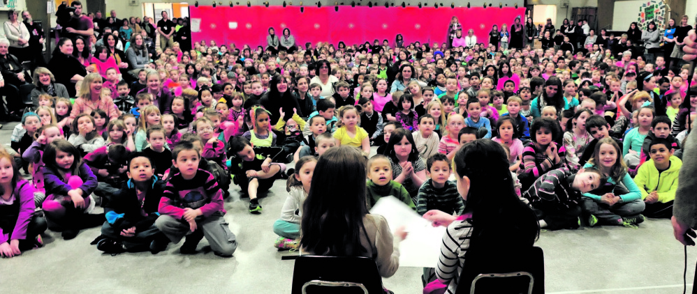 FRUITS OF THEIR LABORS: George J. Mitchell school students Alice Willette, left, and Gabbie St. Peter look over checks and awards they received for the school food pantry as fellow classmates applaud during a recognition assembly Wednesday at the Waterville school.