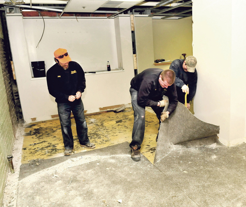 NEW FLOORS: Waterville Public Works employees Joey Meunier, left, Bobby Bellows and Mike Folsom rip up carpet while renovating one of the rooms of the former police department in the basement of City Hall on Thursday.