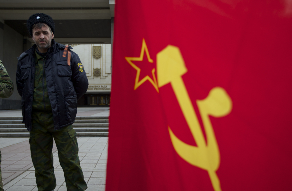 The hammer and sickle are seen on the Soviet flag as members of Cossack militia guard the local parliament building in Simferopol, Ukraine, on Thursday, March 6, 2014. Lawmakers in Crimea declared their intention Thursday to split from Ukraine and join Russia instead, and scheduled a referendum in 10 days for voters to decide the fate of the disputed peninsula. Russia's parliament, clearly savoring the action, introduced a bill intended to make this happen.