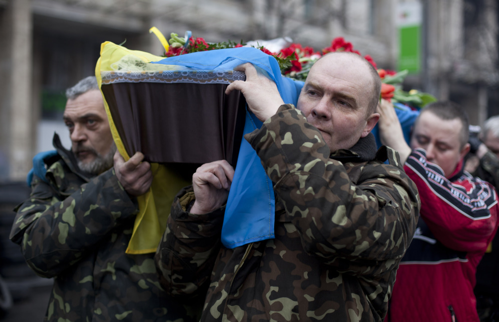 Pallbearers carry a coffin bearing the body Andryi Pozniak, 25, a self defense volunteer who was shot and killed by an unknown assailant two days ago near Kiev's Independence Square, Ukraine, Thursday, March 6, 2014.