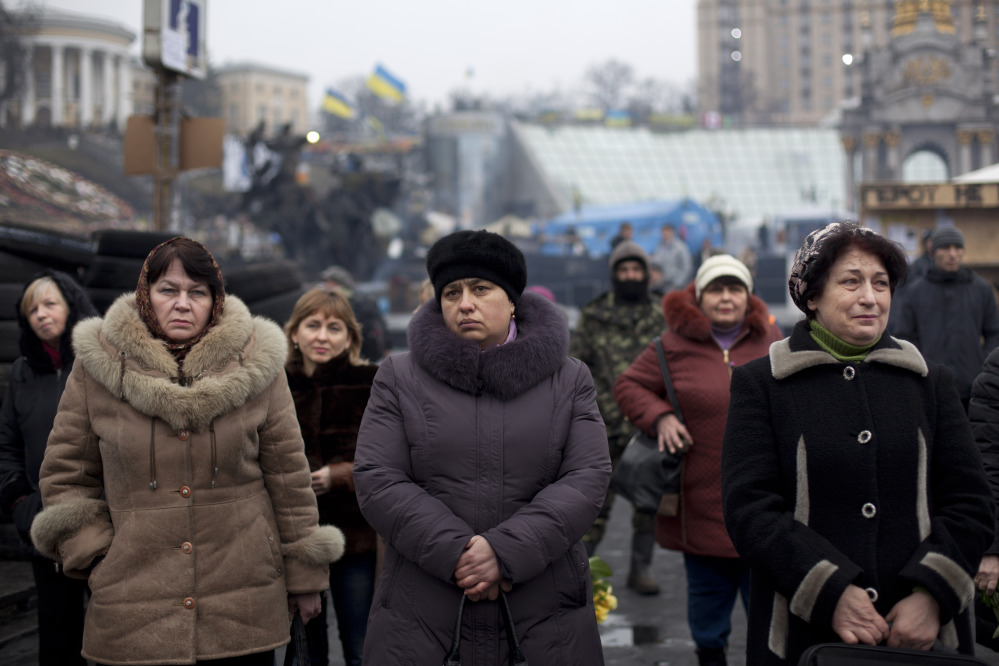 People attend a funeral ceremony for Andryi Pozniak, 25,a self defense volunteer who was shot and killed by an unknown assailant two days ago near Kiev's Independence Square, Ukraine, Thursday, March 6, 2014.