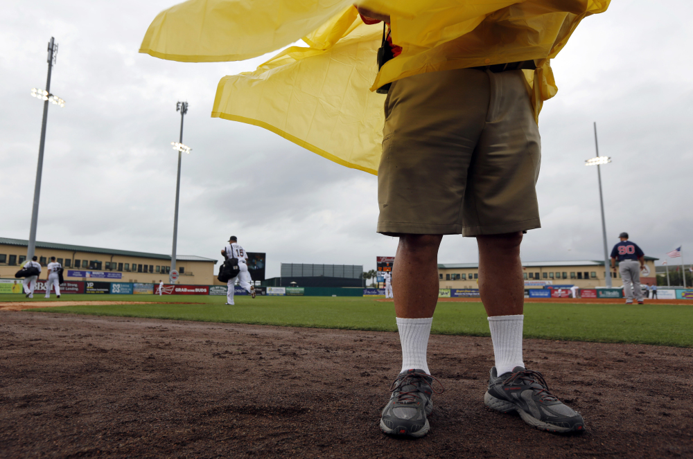 NO FUN: An usher wears a rain poncho as wind kicks up, storm clouds move in and Miami Marlins' Rafael Furcal (15) leaves the field after playing in a spring training game Thursday against the Boston Red Sox, Thursday in Jupiter, Fla. The game was called with a 0-0 score after eight innings.