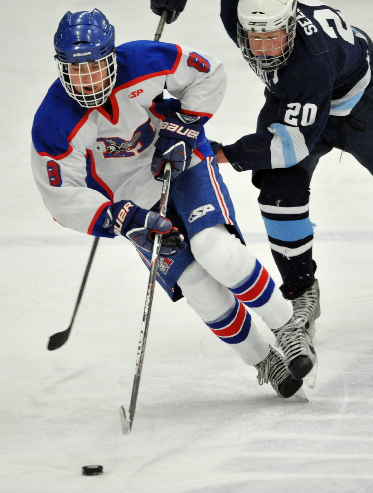 Staff photo by Michael G. Seamans Messalonskee High School's Dylan Burton, 8, controls the puck against Presque Isle High School in the first period of the Eastern B Final game at Alfond Arena at the University of Maine in Orono on Tuesday.