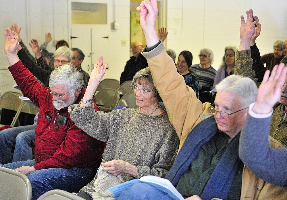 DECISION TIME: Peter Kallin, left, Sue Greenan and Dick Greenan vote from the front row Saturday during the Rome Town Meeting .