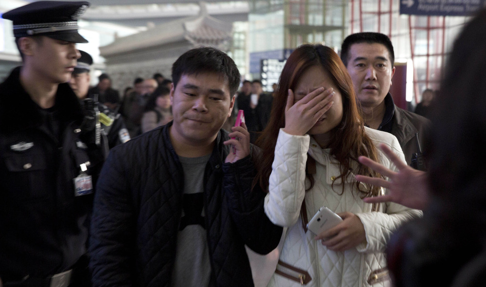 Passengers' friends and family arrive Saturday at the international airport in Beijing for news of a Malaysia Airlines plane that was reported missing on a flight from Kuala Lumpur.