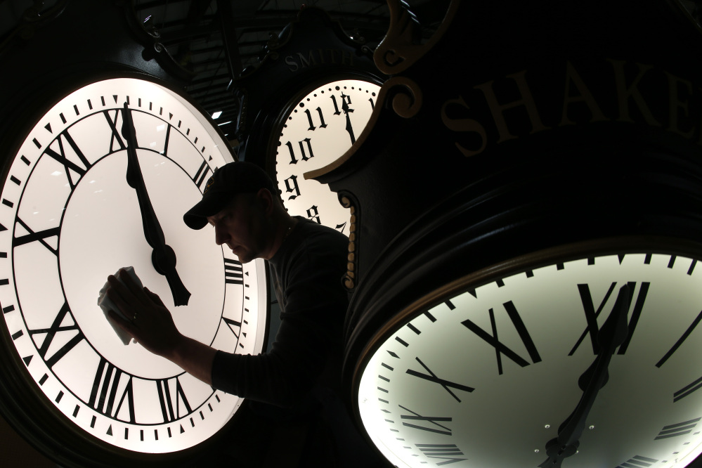 Dave LeMote wipes down a post clock at Electric Time Co. Inc. in Medfield, Mass., on Friday. Most Americans will set their clocks 60 minutes forward before heading to bed Saturday night, but daylight saving time officially starts at 2 a.m. local time Sunday.