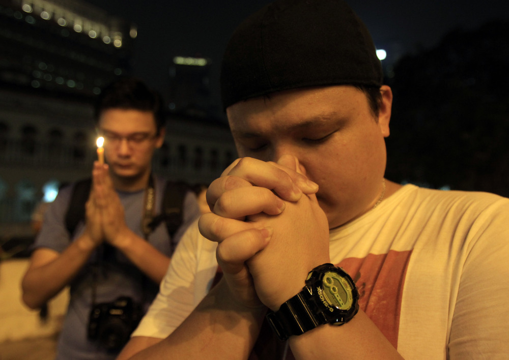 Men offer prayers during a candlelight vigil for passengers aboard a missing Malaysia Airlines plane in Kuala Lumpur, Malaysia, on Monday.