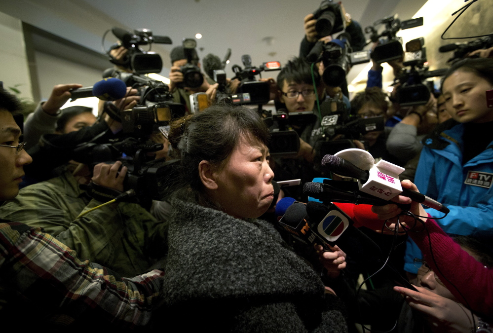 A Chinese relative of passengers aboard a missing Malaysia Airlines plane is surrounded by media in Beijing as she answers questions about how families are being compensated.