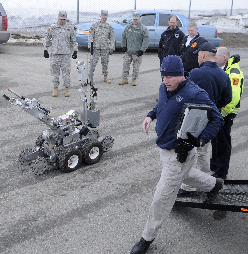 """BLAST STOPPER: State Trooper Shawn Whalen, right, runs to operate a robot Wednesday to search for a bomb at Camp Keyes in Augusta during a drill with state, local and federal emergency agencies at the state headquarters of the Army National Guard. The State Police Bombs/Explosives Unit de-activated a """"weapon"""" behind the Augusta State Airport during the training."""