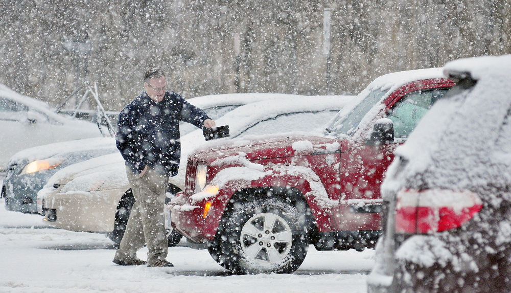 CLEANING UP: Jim Willis cleans off his vehicle after work as snow falls on Wednesday in a parking lot of Water Street in downtown Augusta.