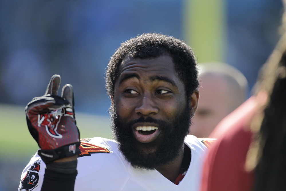 In this file photo, Tampa Bay Buccaneers' Darrelle Revis clowns around with teammates during warm ups before an NFL football game against the Carolina Panthers. Revis has reportedly agreed to a deal with the New England Patriots.
