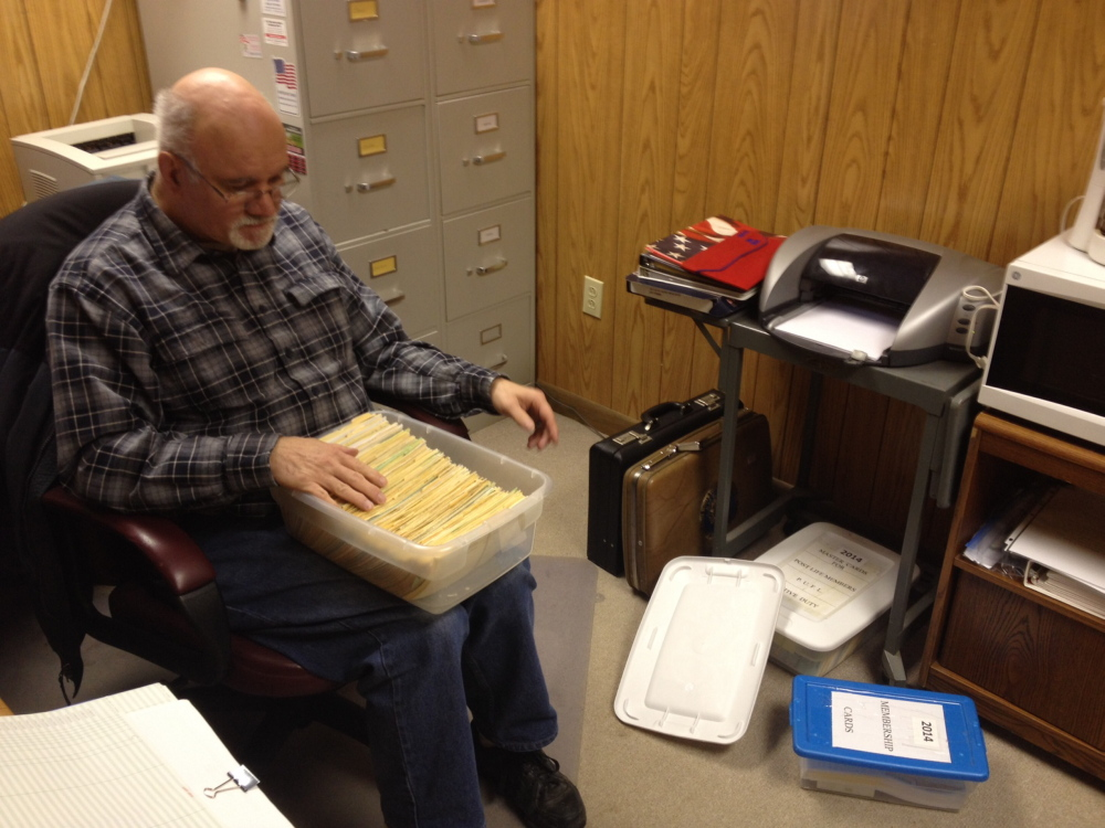 LEGION: Carl Paradis, adjutant of the Bourque-Lanigan American Legion Post, looks through a box of membership information about the Waterville veterans group. Paradis said the post, which is the largest in the state, has lost about 40 members a year and is down to 761 members.