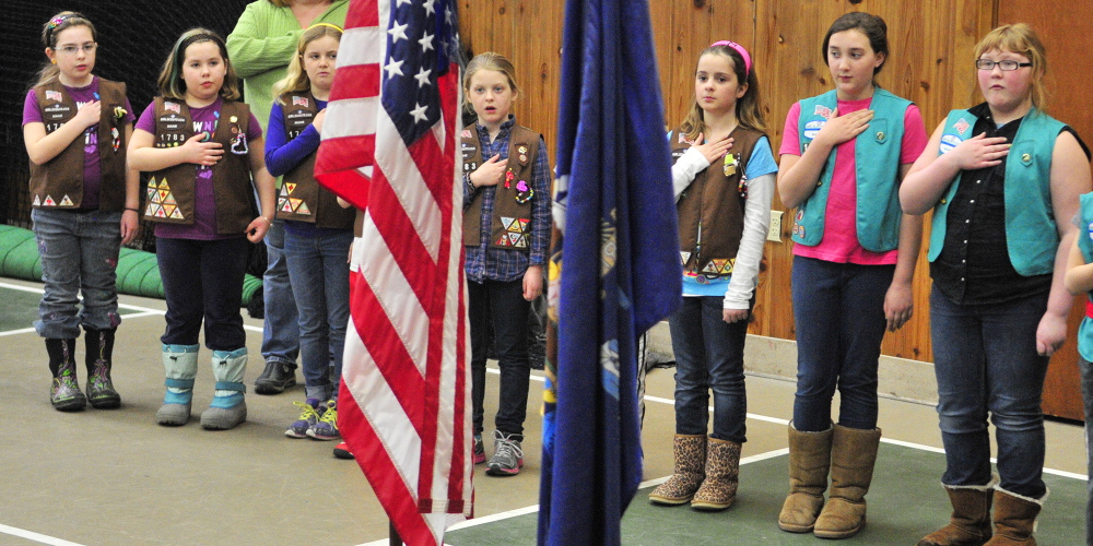 Good deeds of the day: After presenting the colors, members of Brownie Troop 1783 and Girl Scout Troop 1085 lead the Pledge of Allegiance Saturday at the start of the 2014 Belgrade Town Meeting at the Center For All Seasons. The girls also ran a concession stand and helped at the meeting by taking microphones to people speaking from the floor.